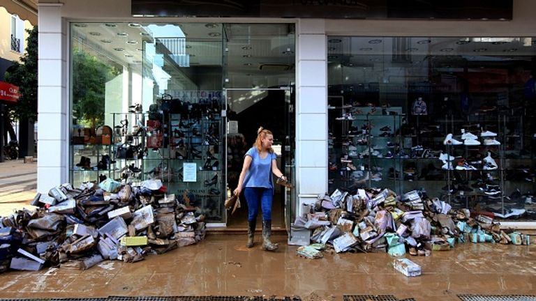 A woman clears the mud from her shop after the floods caused by the Mediterranean hurricane (Medicane) Ianos in Karditsa