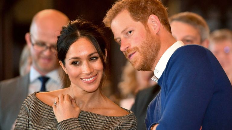 Prince Harry whispers to Meghan Markle as they watch a dance performance by Jukebox Collective in the banqueting hall during a visit to Cardiff Castle in 2018