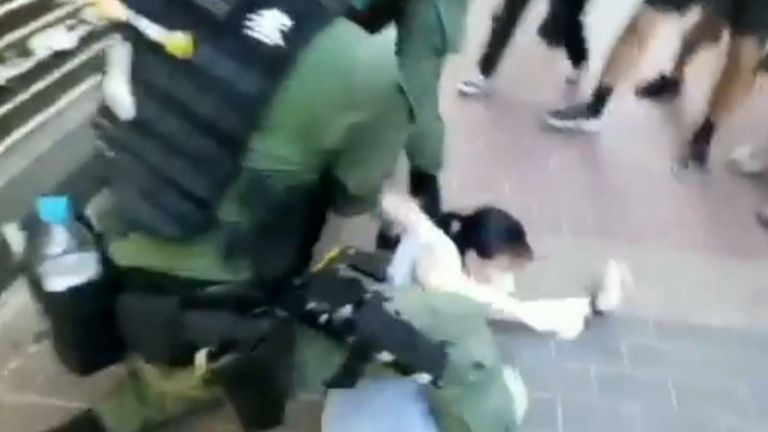 HK police tackle young girl to the ground