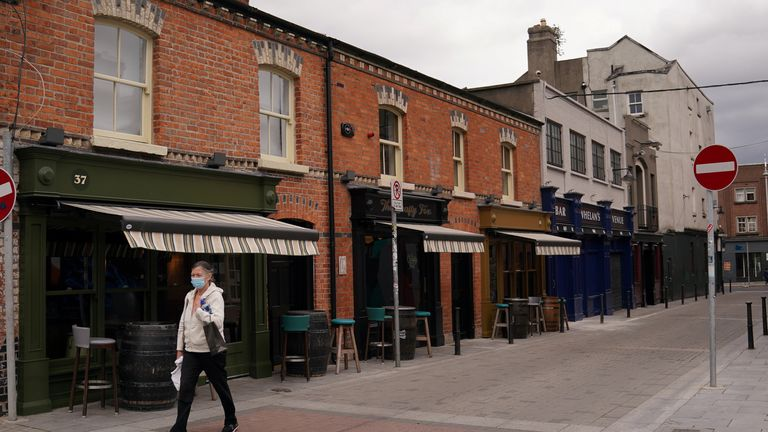 A woman wearing a protective face mask walks through an empty street, amid the coronavirus disease (COVID-19) outbreak in Dublin, Ireland, September 3, 2020.