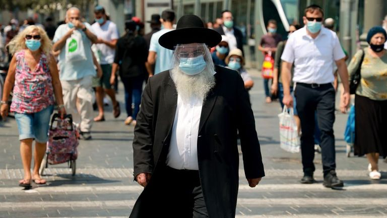 An ultra-Orthodox Jewish man is seen wearing a protective mask and shield in Jerusalem