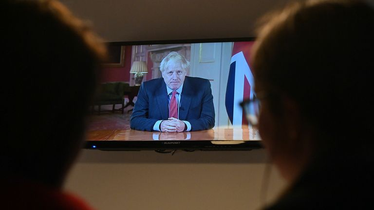 Members of a family watch as Britain's Prime Minister Boris Johnson addresses the nation about the latest updates on the novel coronavirus COVID-19 restrictions, on their television in their home in Liverpool on September 22, 2020. - Britain on Tuesday tightened restrictions to stem a surge of coronavirus cases, ordering pubs to close early and advising people go back to working from home to prevent a second national lockdown.