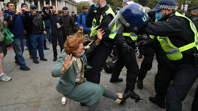 A woman falls as police move in to disperse protesters in Trafalgar Square in London on September 26, 2020, at a 'We Do Not Consent!' mass rally against vaccination and government restrictions designed to fight the spread of the novel coronavirus