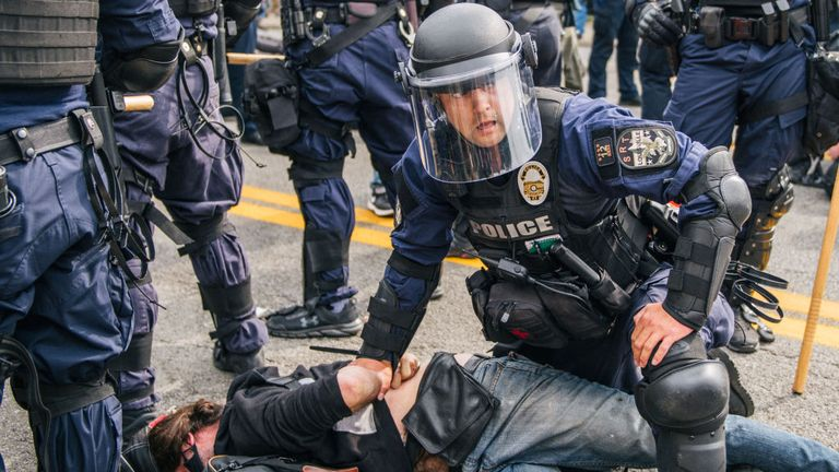 A protester is restrained by an officer in Louisville