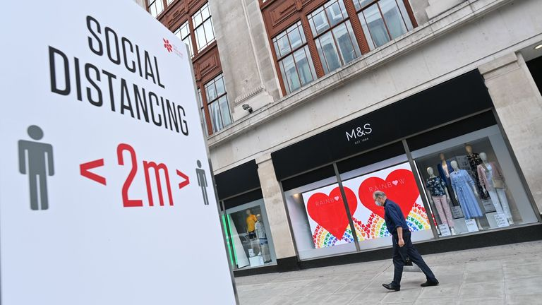 A shopper wearing a facemask as a precaution against the spread of the novel coronavirus walks past a store of the clothing and food retailer Marks and Spencer in central London on August 18, 2020 with social distancing advice displayed on the high street