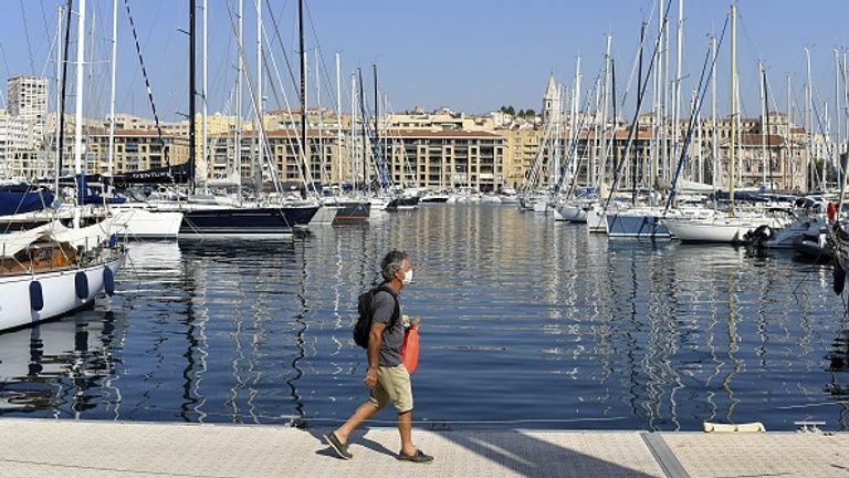 A man wearing a face mask walks on a pier on the Vieux-Port of Marseille