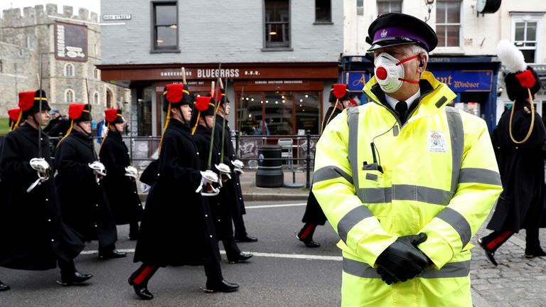 FILE PHOTO: A security guard wearing a face mask stands outside Windsor Castle as the number of coronavirus cases grow around the world, Britain, March 17, 2020. REUTERS/Paul Childs/File Photo