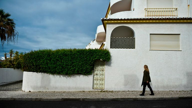A woman passes by the former McCann's apartment at Praia da Luz