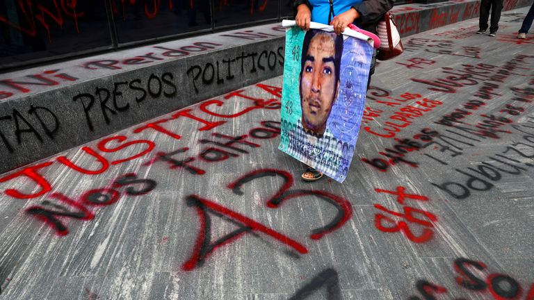 "A relative of a missing student holds a poster with his image as she walks past a ""+43"" sign painted on the ground, during a protest outside the Attorney General's office, before the sixth anniversary of the disappearance of 43 students of the Ayotzinapa Teacher Training College, in Mexico City, Mexico September 25, 2020. REUTERS/Henry Romero"