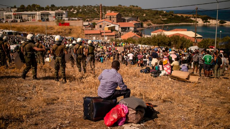 A migrant sits on his belongings