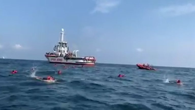 Migrants swim away from Spanish rescue ship Open Arms after more than 70 of them jumped from the ship to attempt to reach the coast, at sea near Palermo, Italy, in this still image taken from video, September 17, 2020. Open Arms/ Handout via REUTERS ATTENTION EDITORS - THIS PICTURE WAS PROVIDED BY A THIRD PARTY. BEST QUALITY AVAILABLE