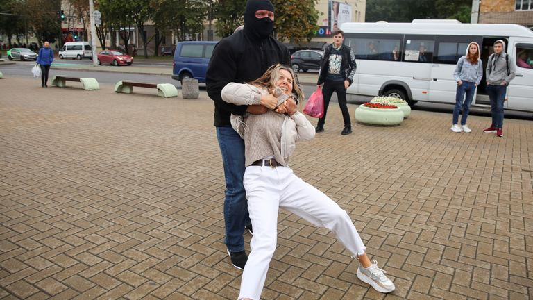 A law enforcement officer drags a demonstrator during a rally in support of detained Belarusian opposition leader Maria Kolesnikova in Minsk