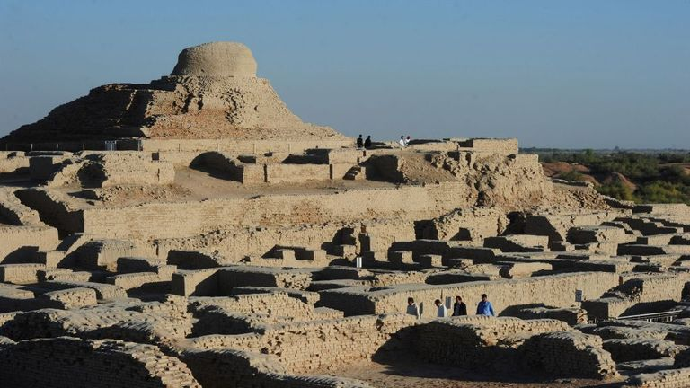 In this photograph taken on February 9, 2017, visitors walk through the UNESCO World Heritage archeological site of Mohenjo Daro some 425 kms north of the Pakistani city of Karachi. Once the centre of a powerful civilisation, Mohenjo Daro was one of the world's earliest cities -- a Bronze Age metropolis boasting flush toilets and a water and waste system to rival modern standards. Some 5,000 years on archaeologists believe the ruins could unlock the secrets of the Indus Valley people, who flouri