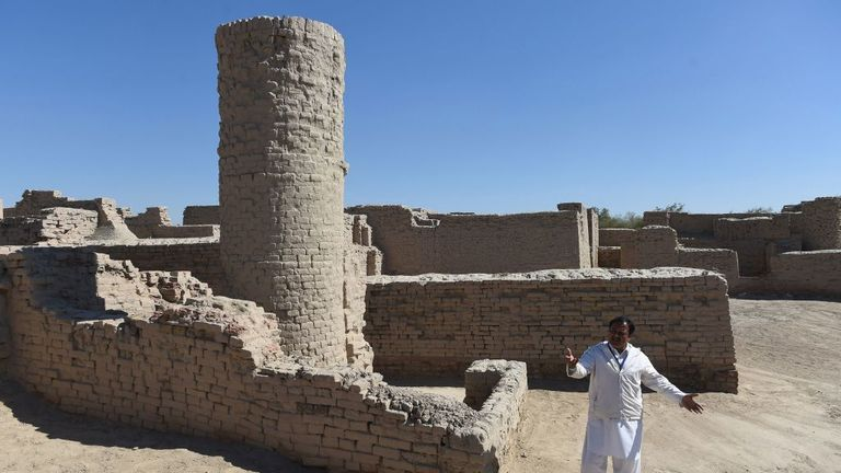 In this photograph taken on February 9, 2017, Pakistani caretaker at the UNESCO World Heritage archeological site of Mohenjo Daro, Ismail Mugheri, points out a two-story well used to collect drinking water at the site some 425 kms north of Karachi. Once the centre of a powerful civilisation, Mohenjo Daro was one of the world's earliest cities -- a Bronze Age metropolis boasting flush toilets and a water and waste system to rival modern standards. Some 5,000 years on archaeologists believe the ru