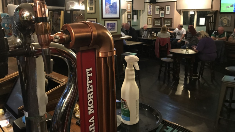 Beer pumps and disinfectant in the subdued Strawberry pub