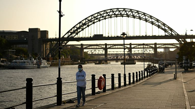 A woman walks near the Tyne Bridge in Newcastle