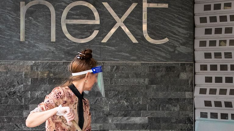 A shop worker cleans the exterior of a Next retail shop on Oxford Street following the introduction of measures to bring England out of lockdown. 11/6/2020