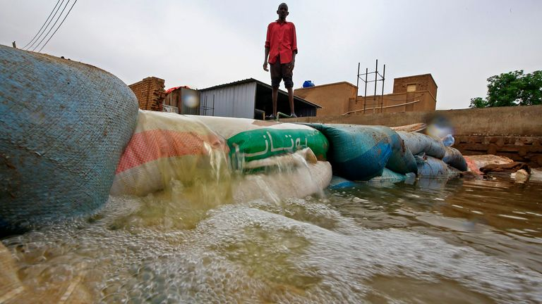 A Sudanese man stands behind a barricade amidst flood waters in Tuti island, where the Blue and White Nile merge between the twin cities of the capital Khartoum and Omdurman, on September 3, 2020