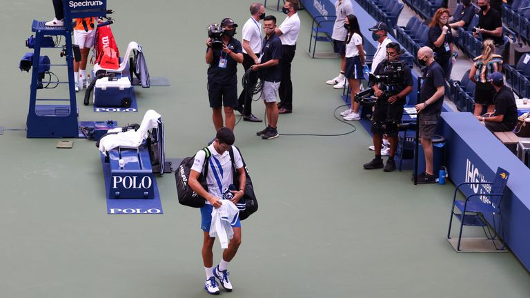 Novak Djokovic walks off court after being disqualified