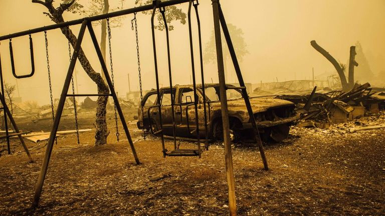 A charred swing set and car after the Santiam Fire swept through in Gates, Oregon