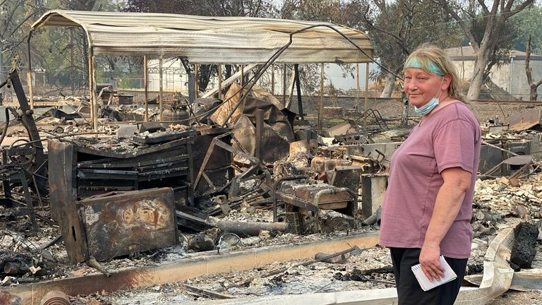 Marcie Barlow next to the charred remains of her home