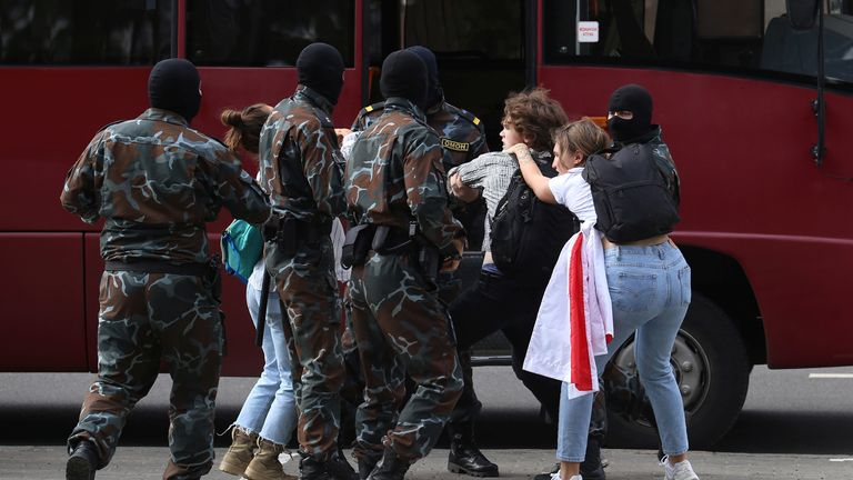 Law enforcement workers are seen detaining students during a protest in Minsk