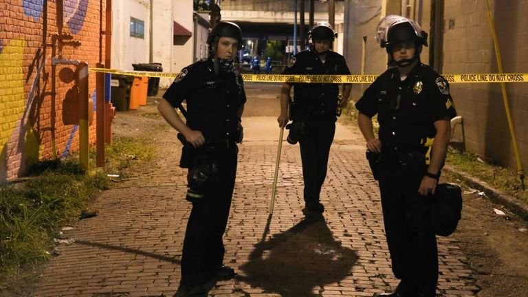 Police officers stand in a taped off area where a policeman was shot as protesters march in Louisville, Kentucky