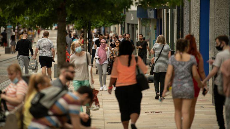 Members of the public walk through the city centre of Preston