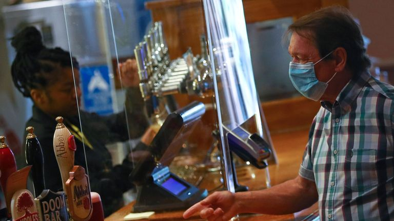 A customer is seen at a bar at The Holland Tringham Wetherspoons pub after it reopened following the outbreak of the coronavirus disease (COVID-19), in London, Britain July 4, 2020