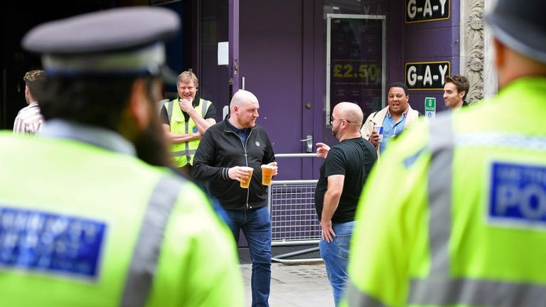 Customers hold drinks as they stand outside re-opened bars, watched by Police officers, in Soho in London on July 4, 2020, as the Soho area embraces pedestrianisation in line with an easing of restrictions during the novel coronavirus COVID-19 pandemic. - Pubs in England reopen on Saturday for the first time since late March, bringing cheer to drinkers and the industry but fears of public disorder and fresh coronavirus cases. (Photo by JUSTIN TALLIS / AFP) (Photo by JUSTIN TALLIS/AFP via Getty I