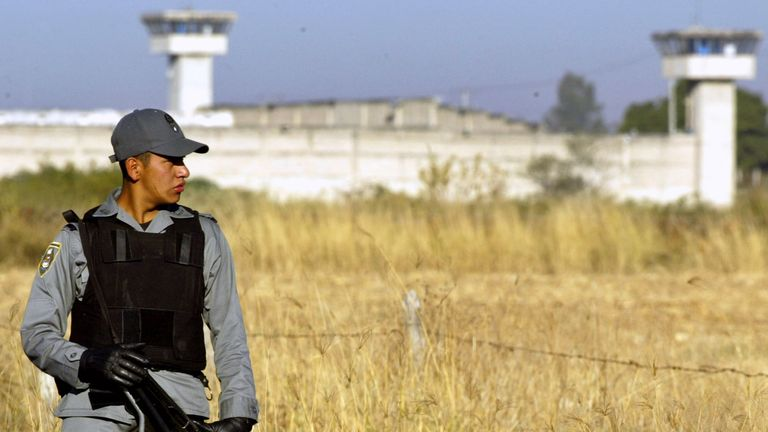 A Mexican Federal Police officer guards the access road to Puente Grande federal prison near Guadalajara w