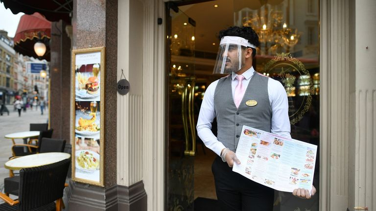 A restaurant employee stands on the step of a restaurant with a menu in the Soho area of London on July 4, 2020, as restrictions are further eased during the novel coronavirus COVID-19 pandemic. - Pubs and restaurants in England reopen on Saturday for the first time since late March, bringing cheer to drinkers and the industry but fears of public disorder and fresh coronavirus cases. (Photo by JUSTIN TALLIS / AFP) (Photo by JUSTIN TALLIS/AFP via Getty Images)