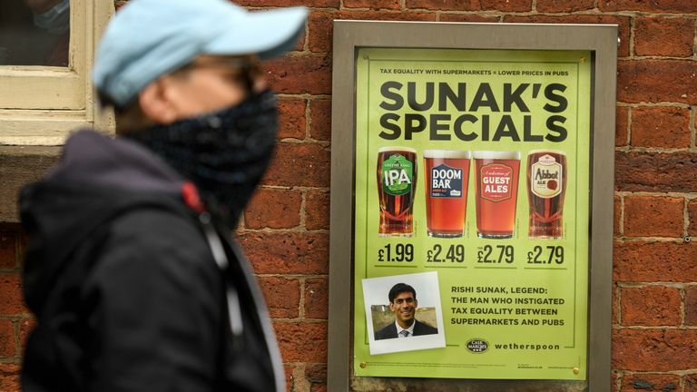 A man walks past a pub advertising 'Sunak's Specials' promotion on beer, referencing the Chancellor of the Exchequer Rishi Sunak in Manchester on August 30, 2020