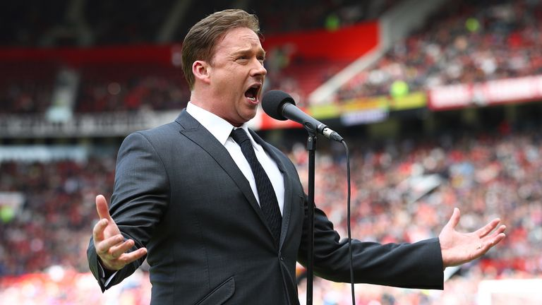 Watson sings ahead of a match at Old Trafford in 2019