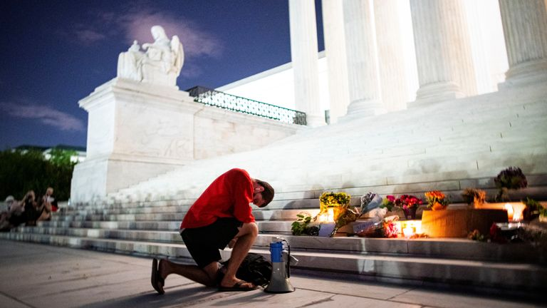 A man kneels at a vigil for Justice Ginsburg