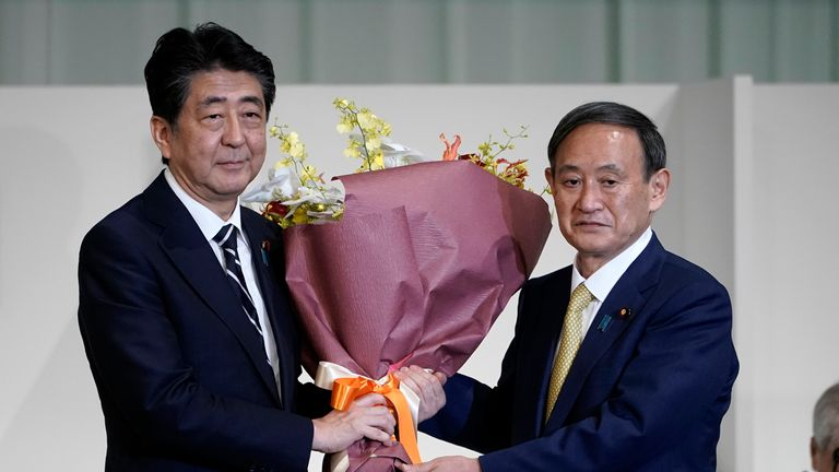 Japan's Prime Minister Shinzo Abe, left, presents Chief Cabinet Secretary Yoshihide Suga flowers after Suga was elected as new head of Japan...s ruling party at the Liberal Democratic Party's (LDP) leadership election Monday, Sept. 14, 2020, in Tokyo. (AP Photo/Eugene Hoshiko, Pool)