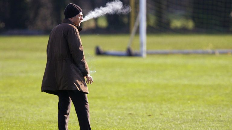 The Croatia national football team manager Slaven Bilic smokes a cigarette as he watches a training session at the club's facility outside Southampton (2007).
