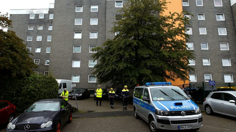 Police officers are seen in front of a residential building where the bodies of five children were found in the western town of Solingen