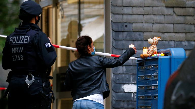 A woman leaves a candle outside the building where the bodies were found