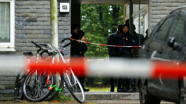 Police officers stand outside a residential building where the bodies of five children were found in the western town of Solingen, Germany