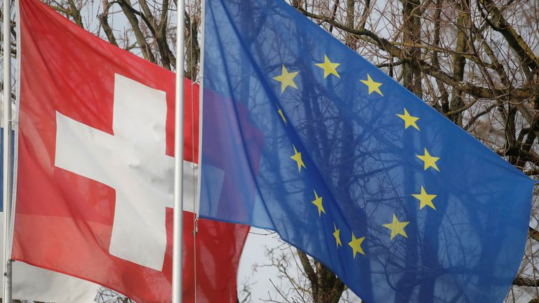 Switzerland's national flag flies beside that of the European Union