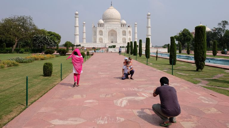 A man gets his photo taken in front of the Taj Mahal after the monument reopens for the first time in six months