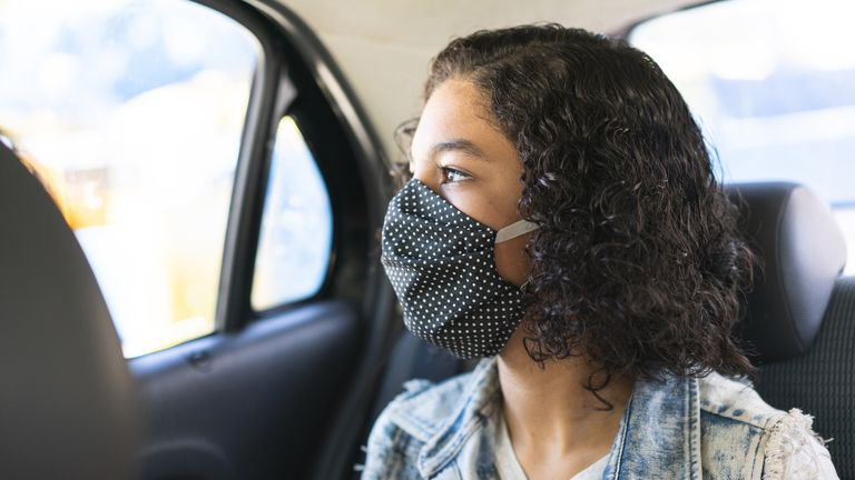 Teenager wearing N95 face mask on car trip stock photo