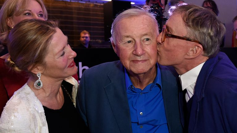 The designer (centre) is kissed by his son, Jasper, as wife Vicki looks on