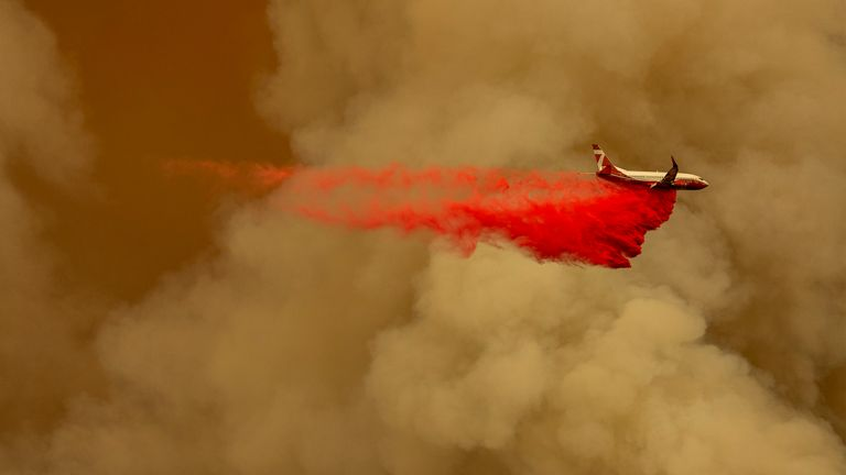 A Coulson 737 firefighting tanker jet drops fire retardant to slow a blaze in the Californian mountains