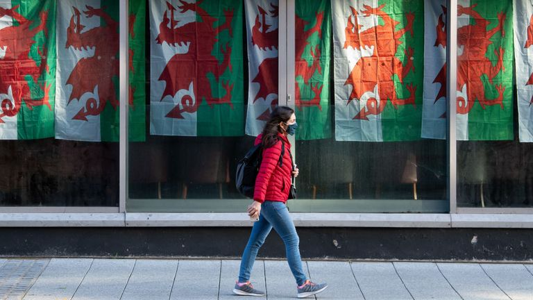 woman wearing a face covering walks past a nightclub in Cardiff