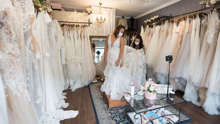 LEIGH-ON-SEA, ENGLAND - JULY 04: Future Bride, Sharni wears a face mask as she tries on wedding dresses in Blush bridal boutique on July 4, 2020 in Leigh-on-Sea, England. Wedding venues reopen today having been closed for over three months in the UK due to the Coronavirus Pandemic. Hairdressers, bars and restaurants will also open all with special measures in place to minimise the risk of spreading Covid-19. (Photo by John Keeble/Getty Images)