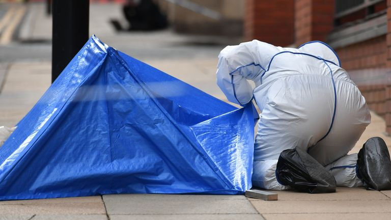 A police forensics officer looks under a small blue police tent on Livery Street in Birmingham after a number of people were stabbed in the city centre