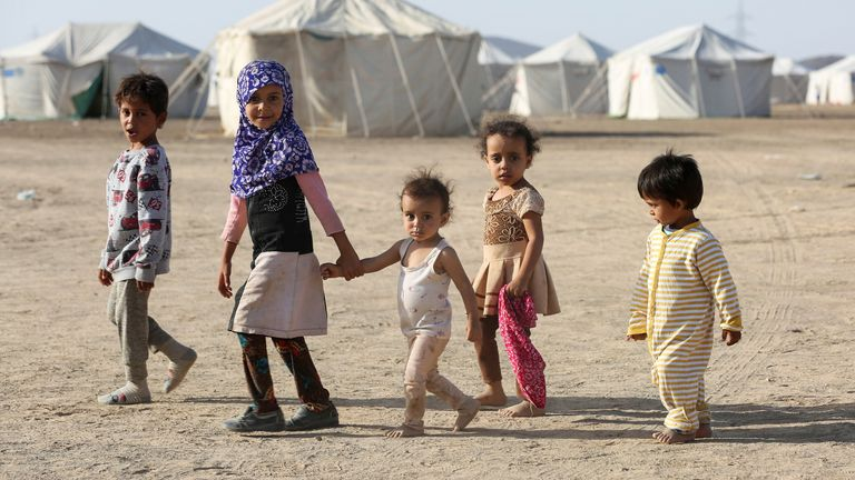 Children walk at a camp for people displaced by fighting in Yemen's northern province of al-Jawf
