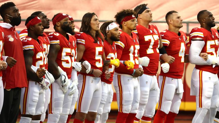 Members of the Kansas City Chiefs stand united with locked arms before the start of a game against the Houston Texans